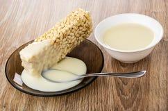 O leite condensado derramou nos arrozes tufados, colher nos pires, bacia com leite na tabela de madeira imagem de stock