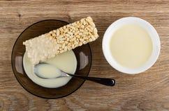 O leite condensado derramou nos arrozes tufados, colher nos pires, bacia com leite na tabela Vista superior foto de stock royalty free
