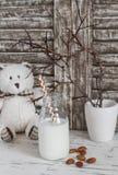 O leite da amêndoa em uma garrafa de vidro, as amêndoas e um brinquedo carregam em uma tabela de madeira clara Fotografia de Stock