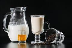 O leite da American National Standard do chá preto é da garrafa do jarro no vidro no fundo preto fotografia de stock royalty free
