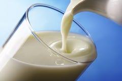 O leite derrama dentro o vidro Imagens de Stock