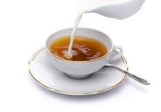 O leite derramou em um copo do chá imagens de stock