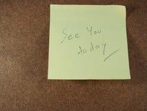 O lembrete, considera-o hoje, escrevendo no papel amarelo da etiqueta Foto de Stock