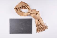O lenço é amarrado na laje bonita do nó e do granito no backgr branco fotografia de stock