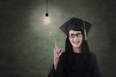 O lerdo bonito no vestido da graduação tem a ideia imagens de stock