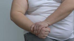 O licenciado gordo que demonstra o braço muscles, fingindo ser muscular, falta do esporte vídeos de arquivo