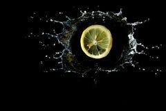 O limão é deixado cair no respingo da água fotos de stock royalty free