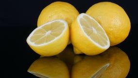 O limão amarelo suculento fresco maduro no fundo preto gerencie filme