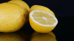 O limão amarelo suculento fresco maduro no fundo preto gerencie vídeos de arquivo