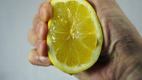 O limão, uma mão espreme o close up do suco vídeos de arquivo