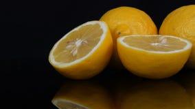 O lim?o amarelo suculento fresco maduro no fundo preto gerencie vídeos de arquivo