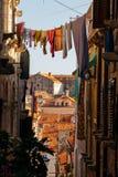 O linho colorido secou em uma corda em uma rua europeia estreita Imagem de Stock