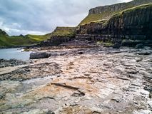 O litoral com as pegadas raras do dinossauro do tracksite sauropod-dominado do nam Brathairean de Rubha, irmãos fotografia de stock royalty free
