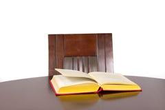 O livro com uma tampa vermelha encontra-se na tabela de madeira marrom Imagem de Stock Royalty Free
