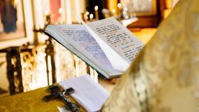 O livro cristão da igreja da leitura do padre, padre lê rezar sobre t imagem de stock royalty free