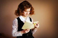 O livro de leitura atento da menina no negócio veste-se no backgro marrom Imagens de Stock