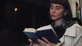 O livro de leitura da jovem mulher ou do passageiro que senta em público o transporte, steadicam disparou Movimento lento A cidad filme