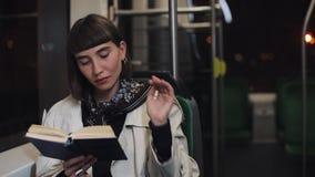 O livro de leitura da jovem mulher ou do passageiro que senta em público o transporte, steadicam disparou Movimento lento A cidad vídeos de arquivo