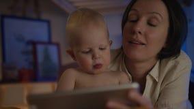 O livro de leitura da mãe a seu bebê que encontra-se na cama com imagens do differend e para dar-lhe deleites relaxa junto filme