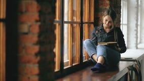 O livro de leitura novo bonito da menina do estudante senta-se na soleira na sala de aula da universidade dentro filme