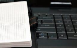 O livro de nota encontra-se no teclado Fotografia de Stock Royalty Free