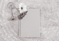O livro de nota marrom do close up com a flor colorida artificial borrada na garrafa de vidro transparente na tabela concreta tex Imagem de Stock Royalty Free