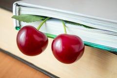 O livro e as cerejas maduras vermelhas Olhar maduro de duas cerejas fora do th Fotos de Stock