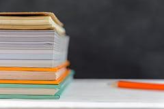 o livro e o lápis na tabela branca enegrecem o fundo da placa com estudo Imagens de Stock