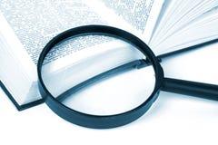 O livro e o magnifier Imagens de Stock