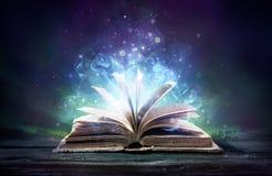 O livro encantado com mágica incandesce fotos de stock royalty free