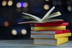 O livro na tabela de madeira e o fundo macio do bokeh do borrão, conceito como o papel da abertura verão o conhecimento do mundo, foto de stock