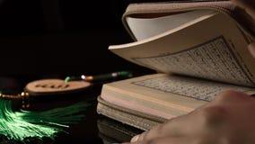 O livro sagrado das mãos do Corão dos muçulmanos guarda o koran Fotografia de Stock