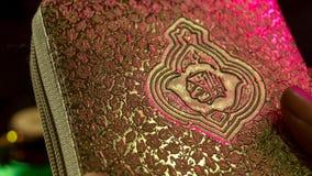 O livro sagrado das mãos do Corão dos muçulmanos guarda o koran Foto de Stock