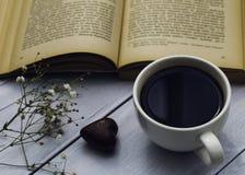 O livro velho, a xícara de café e o coração deram forma ao chocolate Fotos de Stock