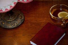 O livro vermelho, o copo com chá e a lâmpada velha do vintage no fundo de madeira apresentam em casa na noite Vista horizontal Es Imagem de Stock Royalty Free