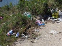 O lixo saiu na terra ao lado do rio fotos de stock