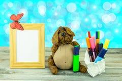 O local de trabalho da criança com cão engraçado está guardando um lápis verde, umas penas coloridas e um quadro vazio com borbol Imagens de Stock