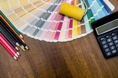 O local de trabalho do escritório com escovas, calcula, lápis e amostras de folha coloridos da cor Fotografia de Stock Royalty Free