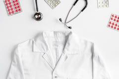 O local de trabalho moderno da medicina com macacão, os meds e o plano branco da tabela do estetoscópio colocam o espaço para o t Foto de Stock