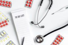 O local de trabalho moderno da medicina com para fazer a lista, comprimidos, plano branco da tabela do estetoscópio coloca o espa Imagem de Stock