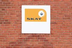 O logotipo dinamarquês da autoridade de imposto em uma parede chamou Skat no dinamarquês fotografia de stock royalty free