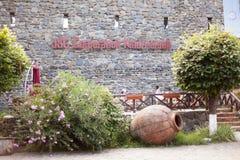 O logotipo do ` s do corporaçõ do vinho de Kindzmarauli em uma parede de pedra Fotografia de Stock Royalty Free