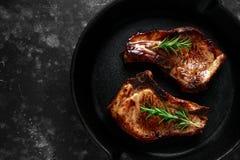 O lombo de carne de porco cozinhado desbasta no frigideira rústico, bandeja com alecrins Vista superior Fundo fotografia de stock royalty free