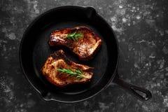 O lombo de carne de porco cozinhado desbasta no frigideira rústico, bandeja com alecrins Vista superior Fundo imagens de stock