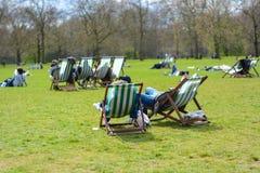 o londrino senta-se em deckchairs em Hyde Park Londres, Inglaterra Foto de Stock