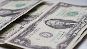 O lote de notas de dólar pequenas cai na tabela com um fim branco do macro do fundo acima video estoque
