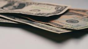 O lote de notas de dólar pequenas cai na tabela com um fim branco do macro do fundo acima filme