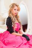 O louro à moda no vestido vermelho longo está sentando-se na cama Foto de Stock