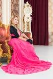 O louro à moda no vestido vermelho longo está sentando-se no sofá luxuoso Imagens de Stock