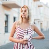 O louro alegre bonito da jovem mulher em um vestido listrado cor-de-rosa na moda está estando na cidade e está bebendo um cocktai imagens de stock